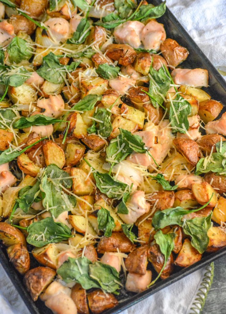 Roasted Chicken and Vegetable Sheet Pan Supper shows spinach, chopped chicken, and roasted potatoes cooked on a single pan and topped with shredded Parmesan cheese