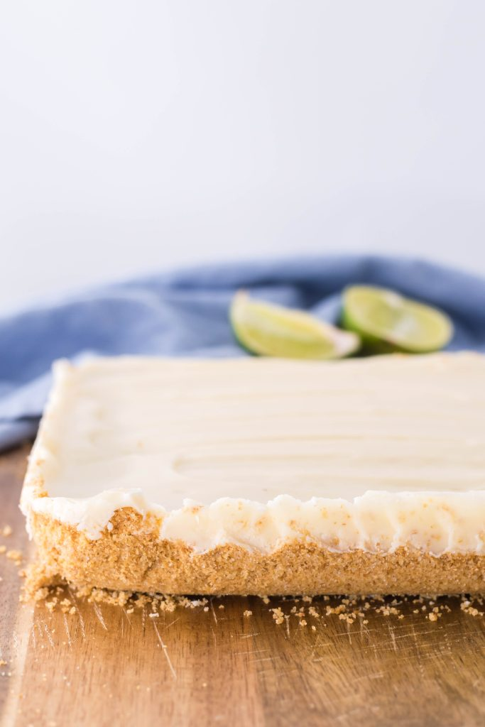a slab of key lime pie fudge shown on a wooden cutting board with sliced limes in the background