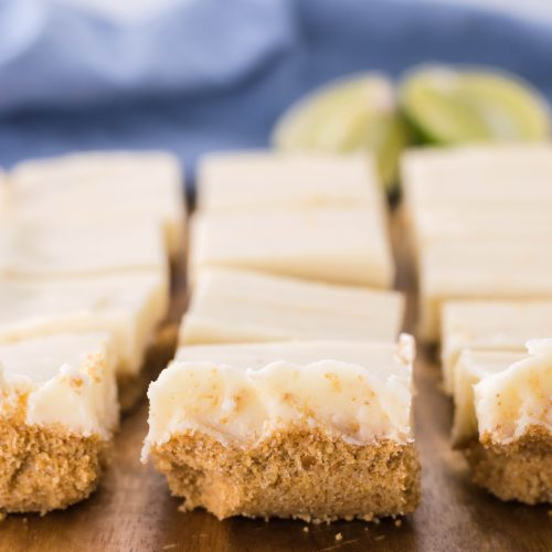 a slab of key lime pie fudge shown on a wooden cutting board with fresh sliced lime wedges in the background