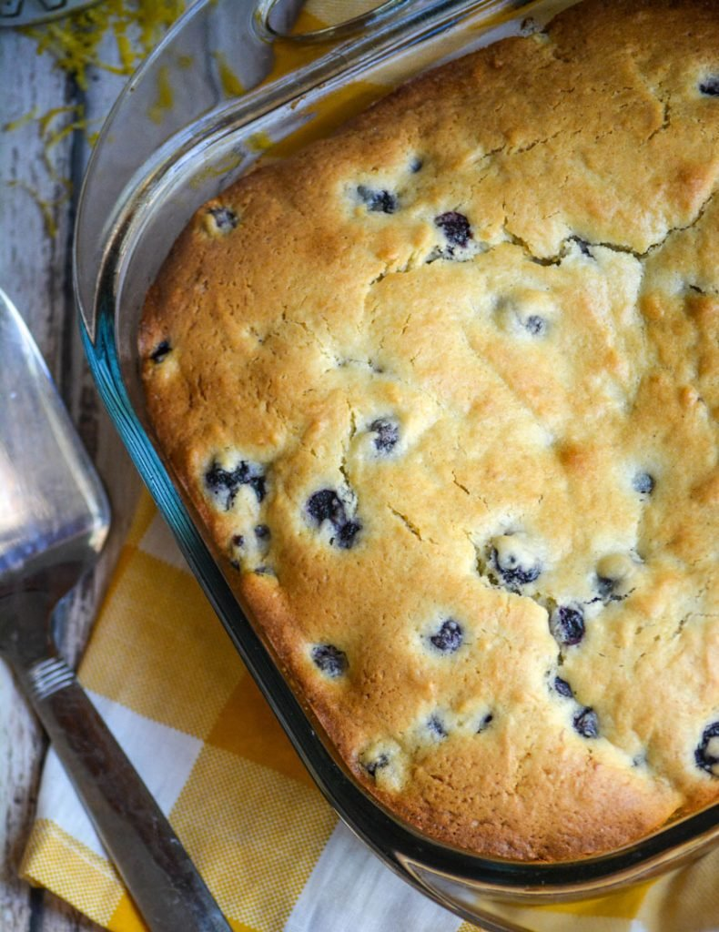 buttermilk blueberry breakfast cake on a wooden picnic table with yellow checkered napkin and metal spatula