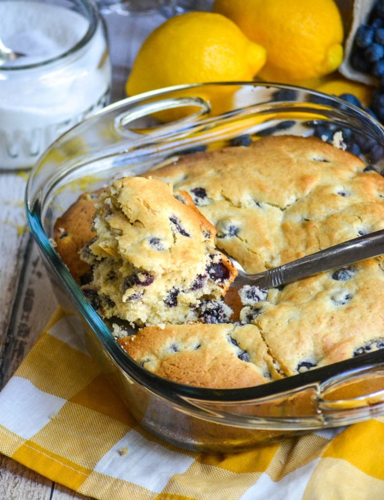 blueberry buttermilk breakfast cake with a slice being removed and lemons in the background