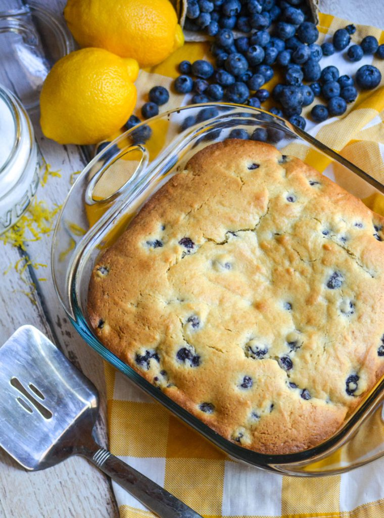 blueberry cake for breakfast on a yellow checkered napkin with fresh lemon, blueberries, and a metal spatula