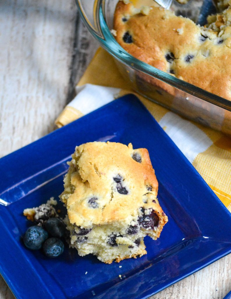 a slice of blueberry breakfast cake on a small blue square plate with fresh blueberries