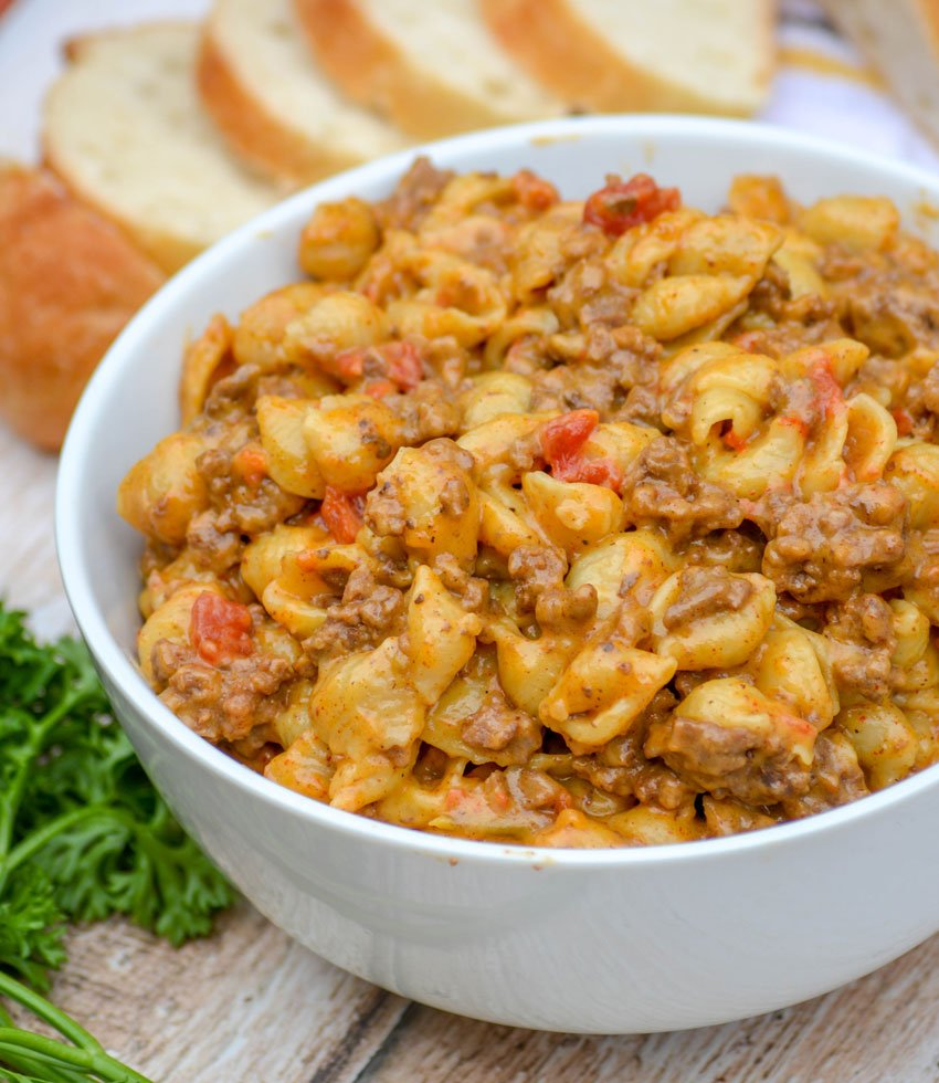 creamy cheesy shell pasta with ground beef and tomatoes in a white bowl on a wooden background with sliced bread and fresh parsley in the background
