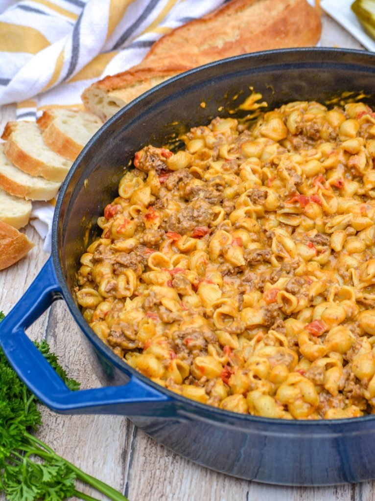 beef and shell shaped pasta with tomatoes in a cheesy sauce in a blue enameled dutch oven on a wooden background. Fresh parsley, a partially sliced baguette, and a striped dish cloth are in the background.