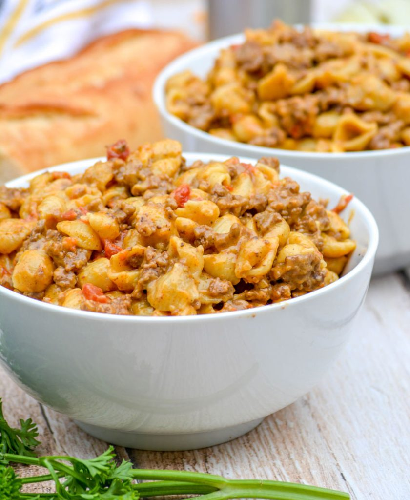 shell pasta in a creamy cheese sauce with ground beef and tomatoes is show in two white bowls on a wooden background with fresh parsley & bread in the background