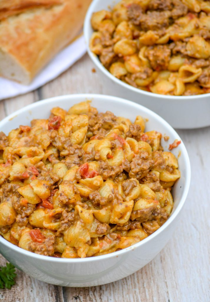beef and shell shaped pasta with tomatoes in a cheesy sauce in two white bowls on a wooden background with a fresh baguette in the background.