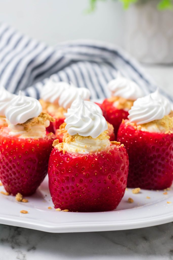 whipped cream topped cheesecake stuffed strawberries on a white plate on marble counter with striped dish cloth and plant in background