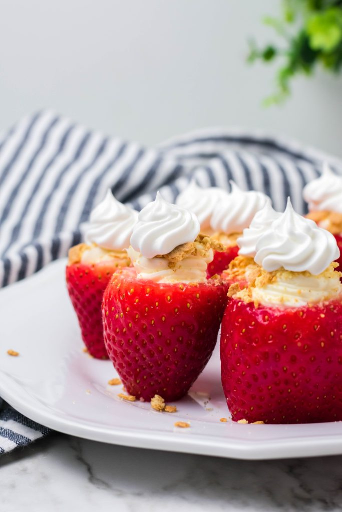 cheesecake stuffed strawberries on a white plate on marble background with a striped dish cloth and plant behind them