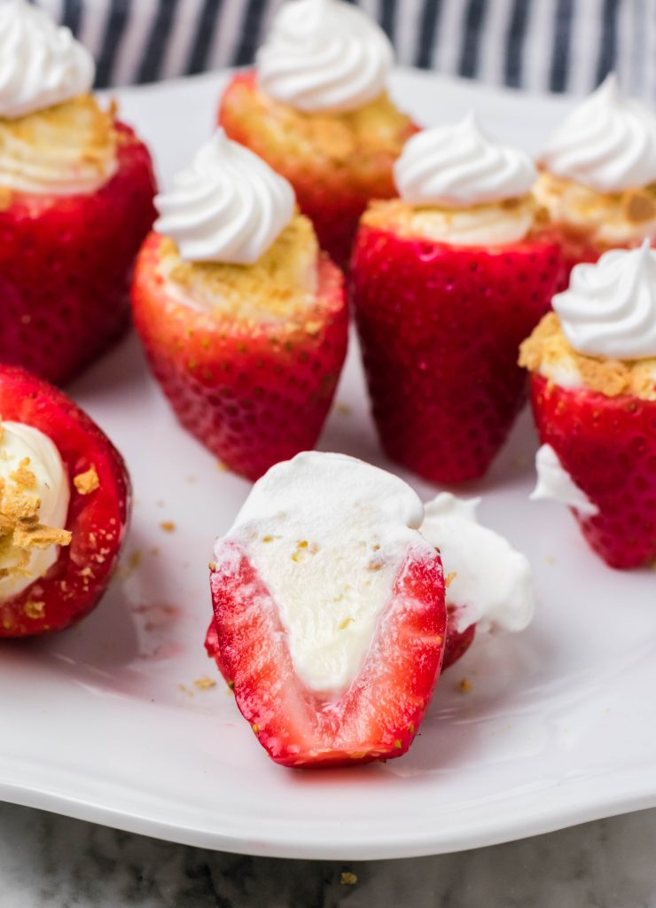 cheesecake stuffed strawberries on a white plate with one cut in half to show the filled inside