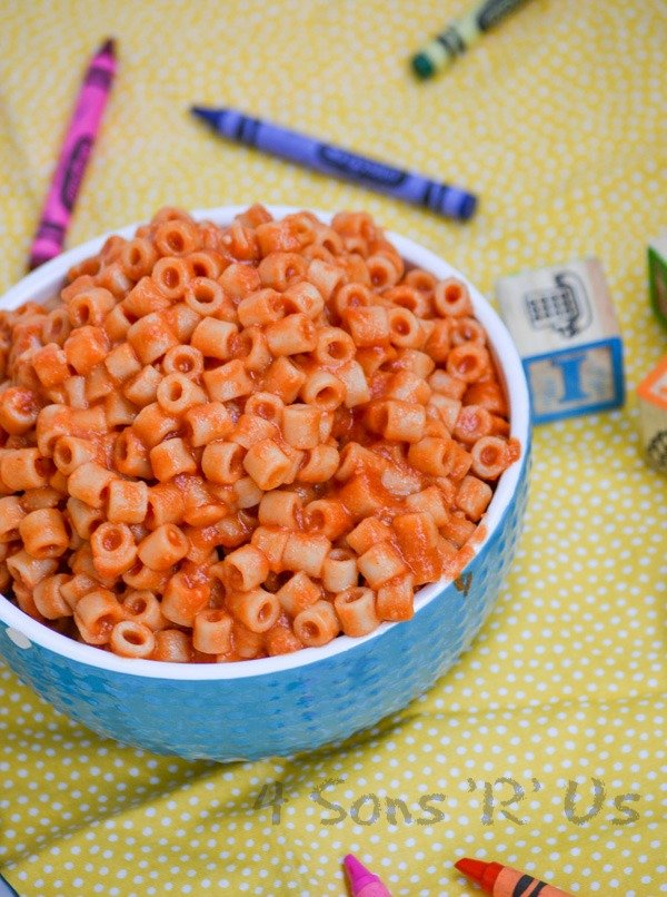 Homemade Spaghetti O's in a white rimmed blue bowl on a yellow background with crayons and wooden toy blocks