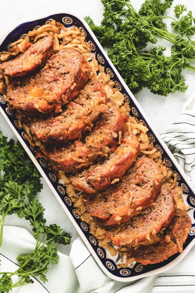 slices of bacon cheeseburger meatloaf with melted cheddar in the center on a white & blue patterned rectangular serving dish with french fried onions around it and fresh parsley in the background