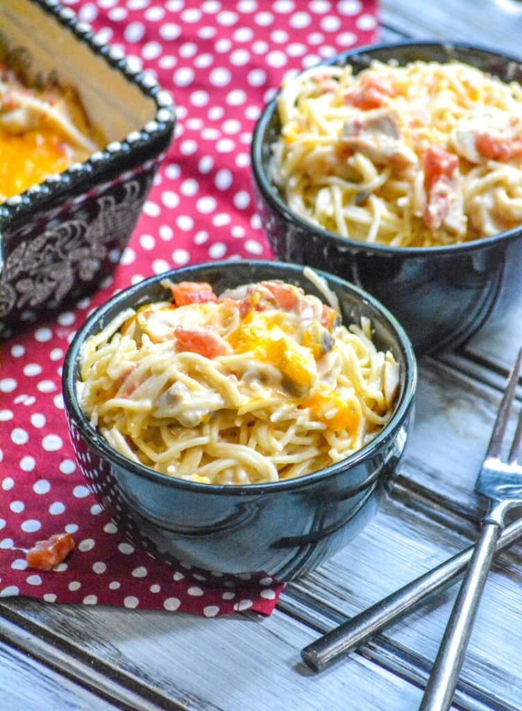 Cheesy Mexican Chicken Spaghetti in two black bowls on a wooden backdrop with a red and white polka dotted cloth napkin