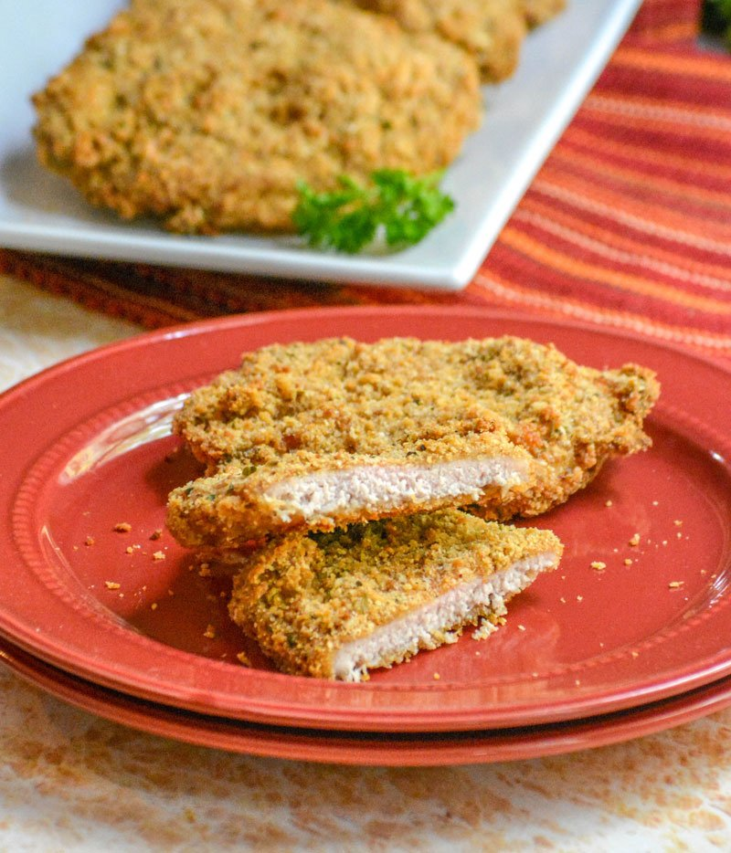 Crispy, Baked Italian Ranch Pork Chops sliced in half on a stack of red plates