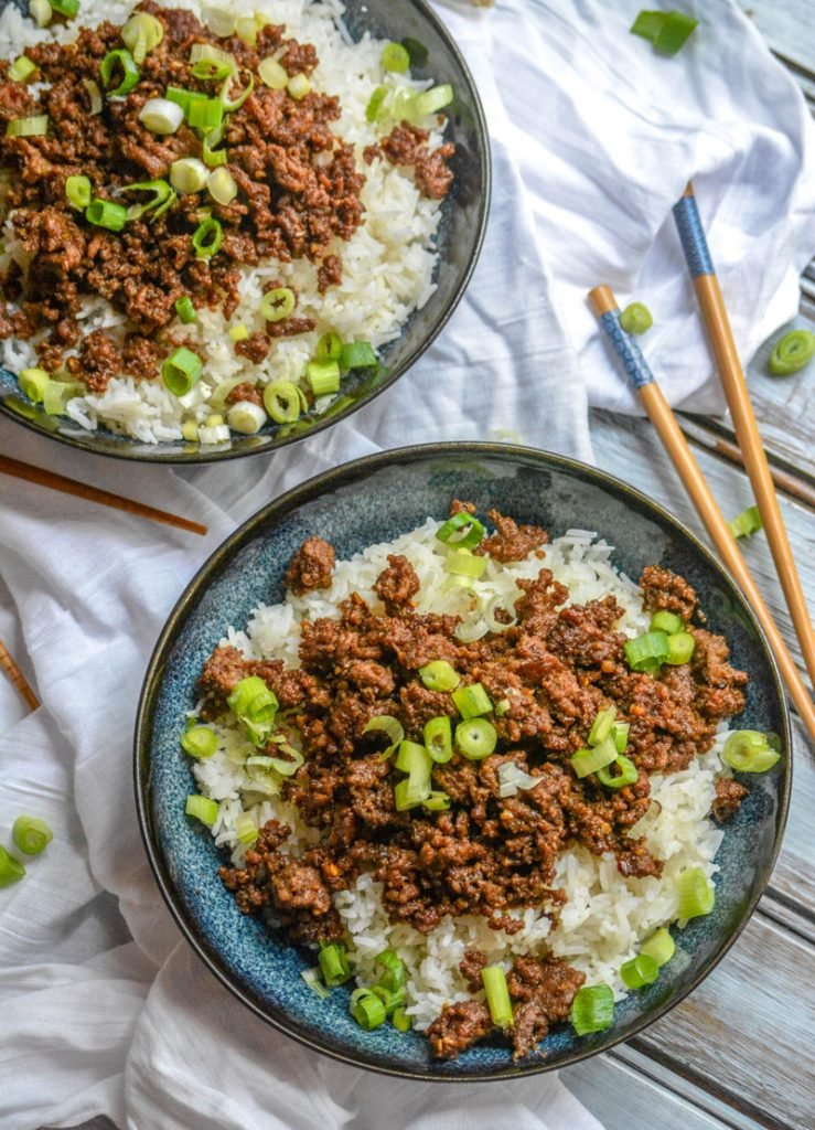 Korean Beef with sliced green onions over steamed white rice in blue bowls