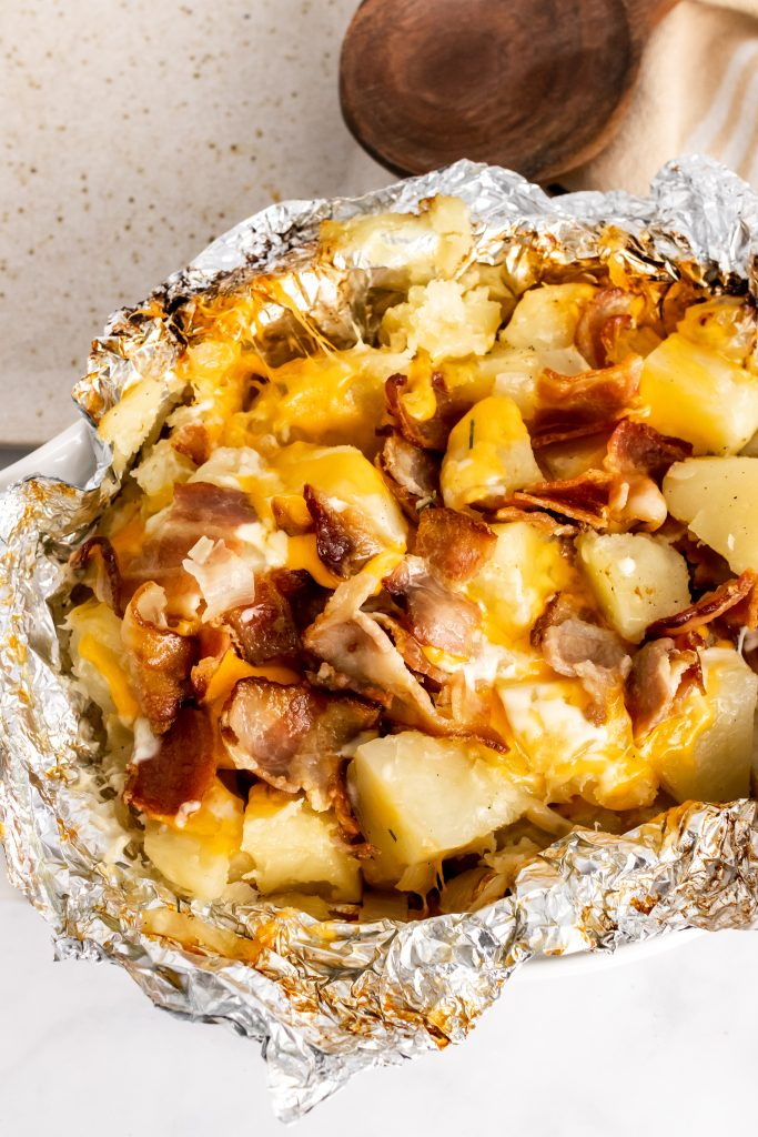 a foil packet torn open to reveal grilled potatoes covered in a blend of melted cheeses