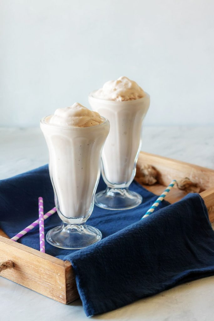 Copy Cat Wendy's Frosty in two high milkshake glasses in a wooden serving tray with a dark blue cloth napkin