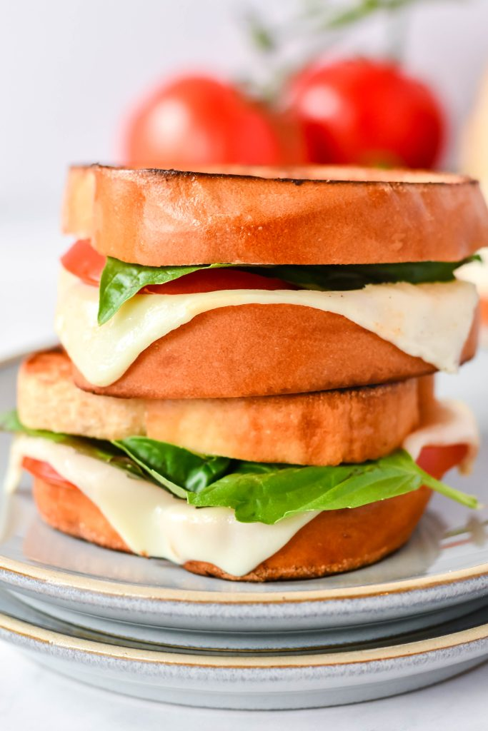 caprese grilled cheese on a stack of gray lunch plates with vine ripened tomatoes in the background