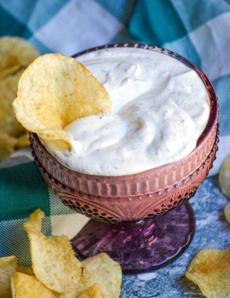 creamy dill dip in a purple glass serving dish with a potato chip stuck in for dipping