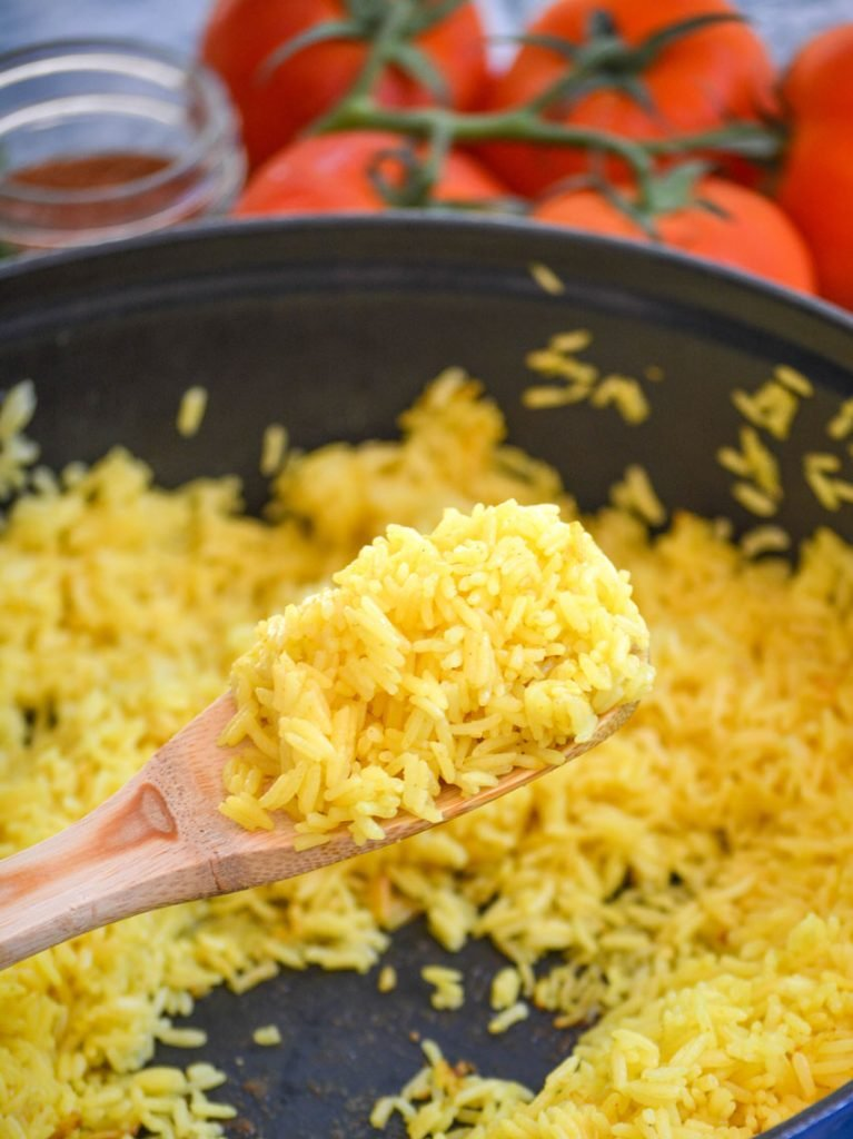 yellow basmati rice held aloft on a wooden spoon with vine ripened tomatoes in the background