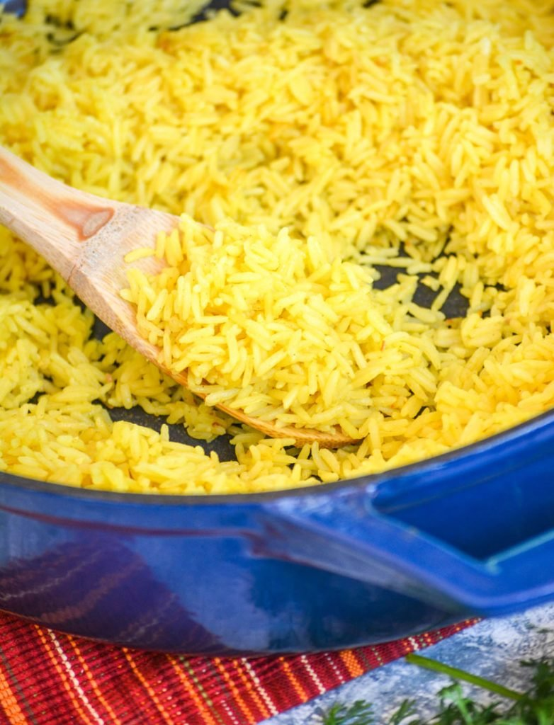 yellow basmati rice scooped on a wooden spoon in a blue enameled cast iron skillet