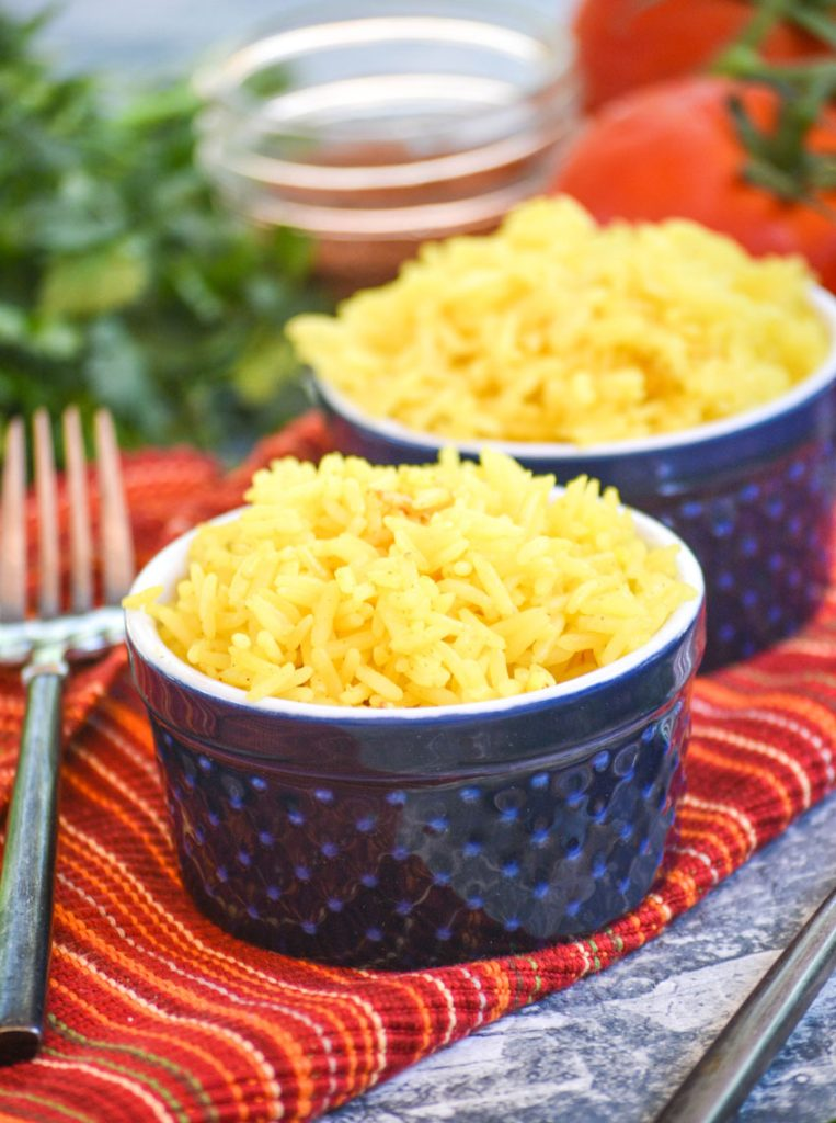 yellow basmati rice in blue ramekins on a cloth napkin with vine ripened tomatoes and fresh cilantro in the background