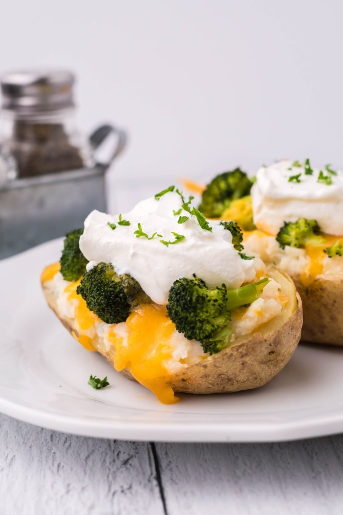 broccoli & cheddar twice baked potatoes topped with a dollop of sour cream and chives served on a white plate