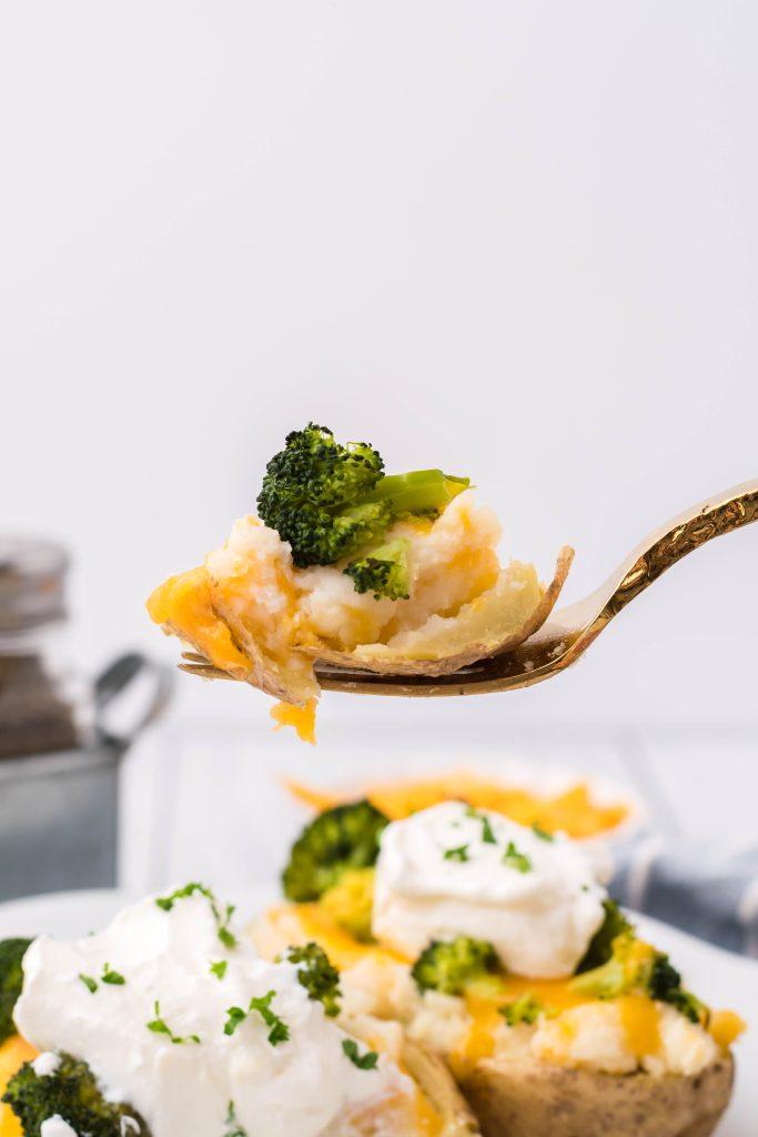 a gold fork holding up a bite of broccoli cheddar twice baked potato