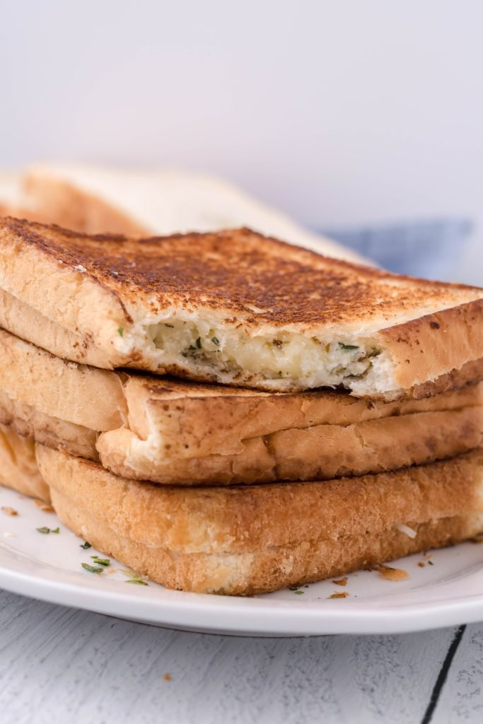 a stack of white pizza grilled cheese sandwiches on a white plate