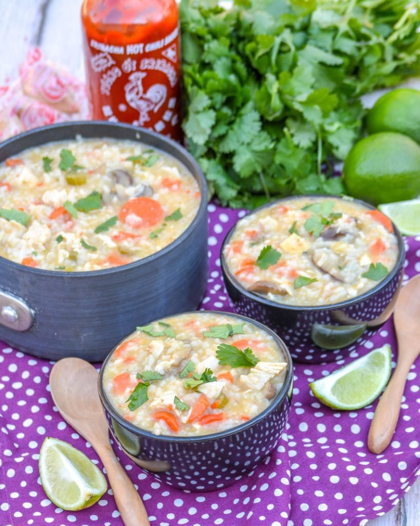 thai chicken coconut soup in a soup pot and shown in two small black bowls, topped with fresh cilantro leaves