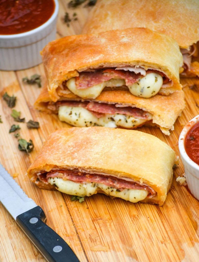 three meat & cheese stromboli shown in slices on a wooden cutting board