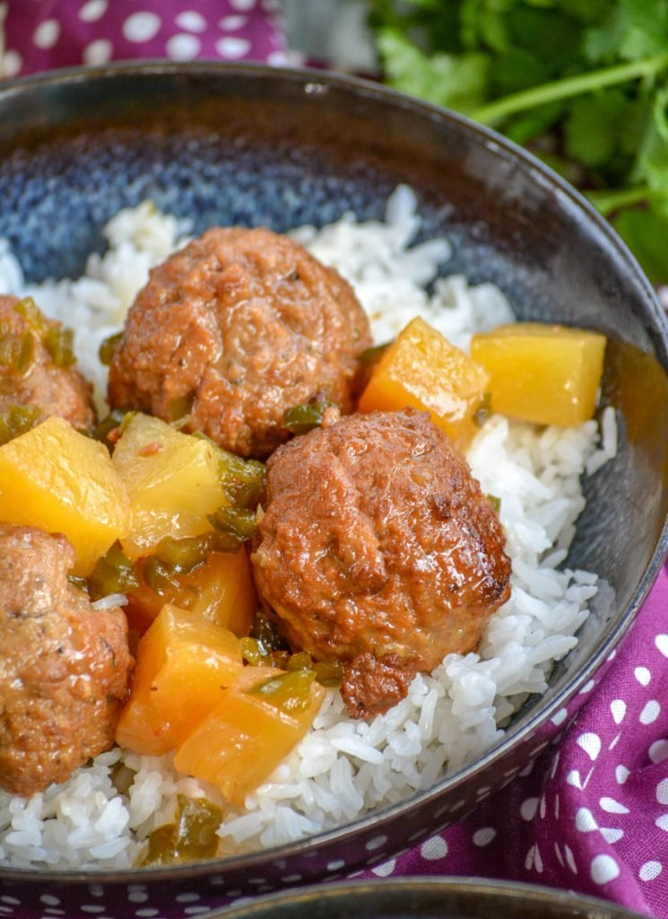 Crockpot Hawaiian Meatballs over a bed of rice in glazed bowl