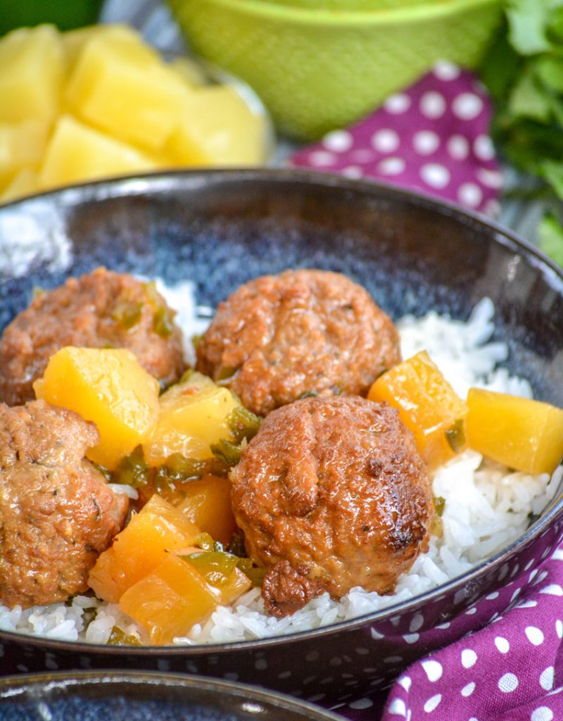 Crockpot Hawaiian Meatballs over a bed of rice in glazed bowl on a purple napkin with fresh pineapple in the background