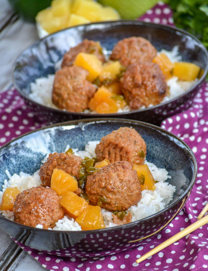 Crockpot Hawaiian Meatballs over a bed of rice in glazed bowls