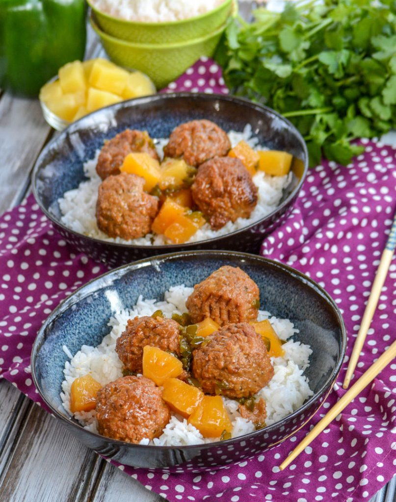 Crockpot Hawaiian Meatballs over a bed of rice in glazed bowls on a purple napkin with chop sticks and fresh herbs in the back ground