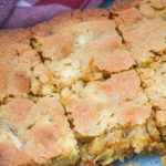 caramel apple blondies shown sliced into bars in a glass baking dish