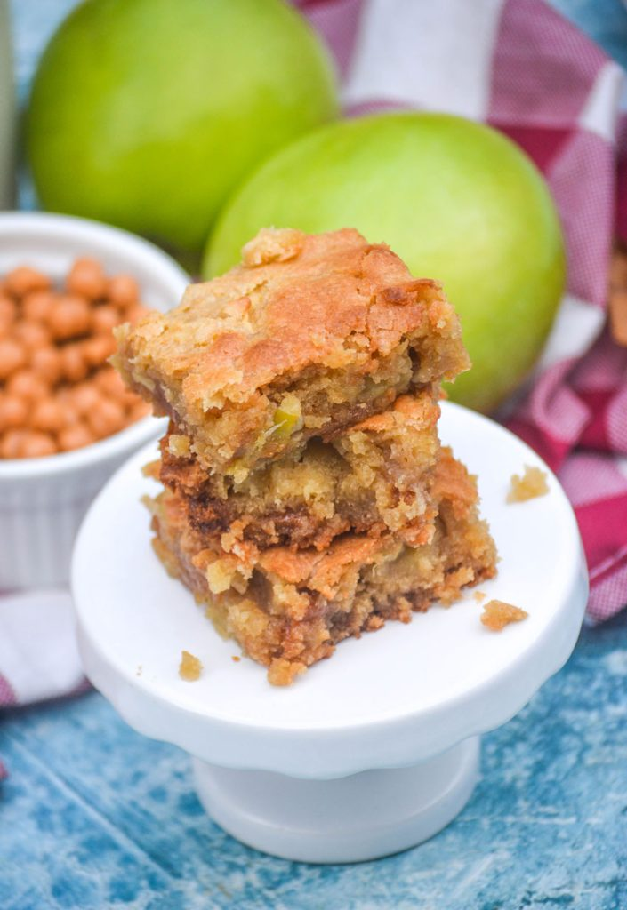 a stack of caramel apple blondies on a white square appetizer plate with whole apples in the background
