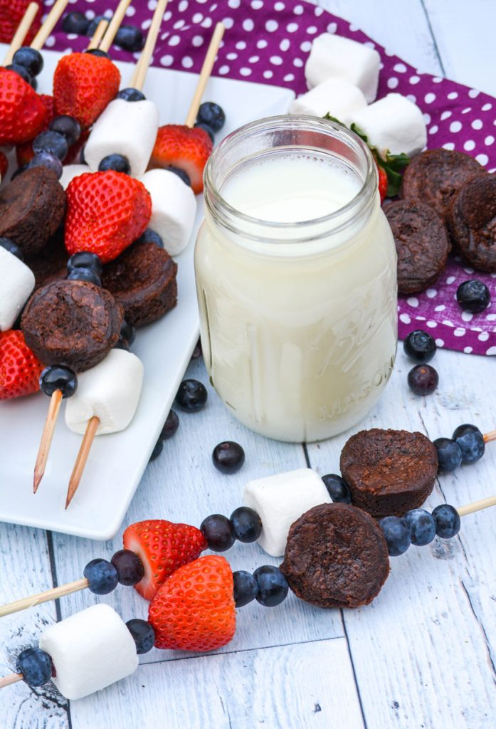 dessert kabobs on wooden skewers shown on a white platter and wooden background with a glass of milk and fresh berries in the background