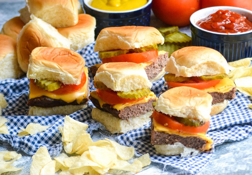 easy cheeseburger sliders next to chips on a blue checkered napkin