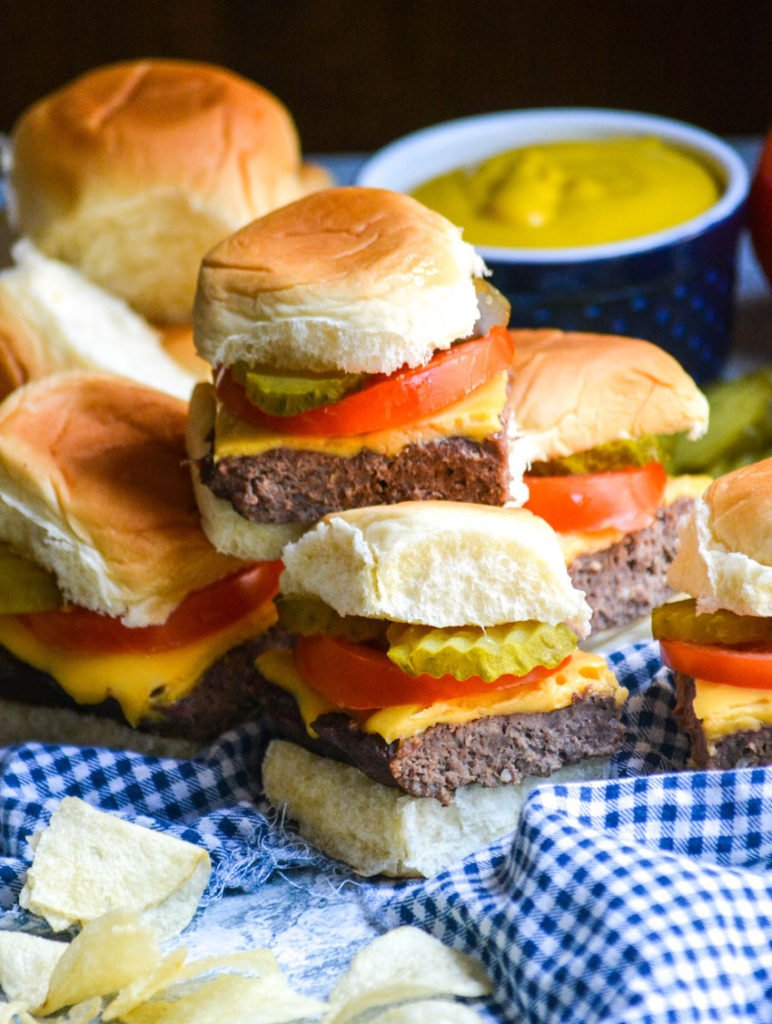 four cheeseburger sliders stacked on top of a blue checkered cloth napkin