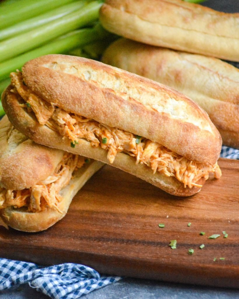 crockpot buffalo chicken sandwiches shown stacked on a wooden cutting board with rolls and crisp celery stalks in the background