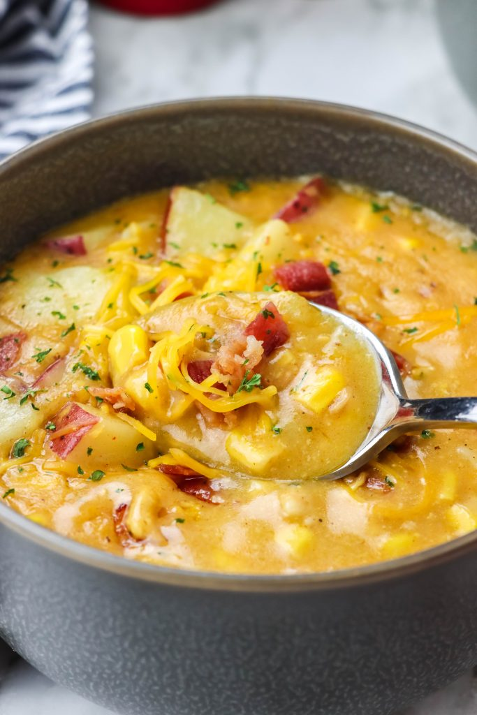 a silver spoon shown scooping up a spoonful of creamy, corn filled instant pot smoky bacon and cheddar chowder