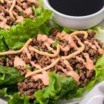 sriracha beef lettuce wraps drizzled with sauce and served on a white plate with a cup of soy sauce