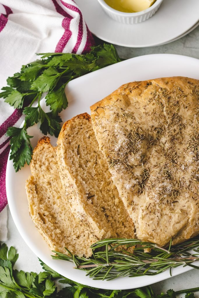 a loaf of crockpot rosemary & olive oil bread shown sliced on a white platter with fresh herbs on the side