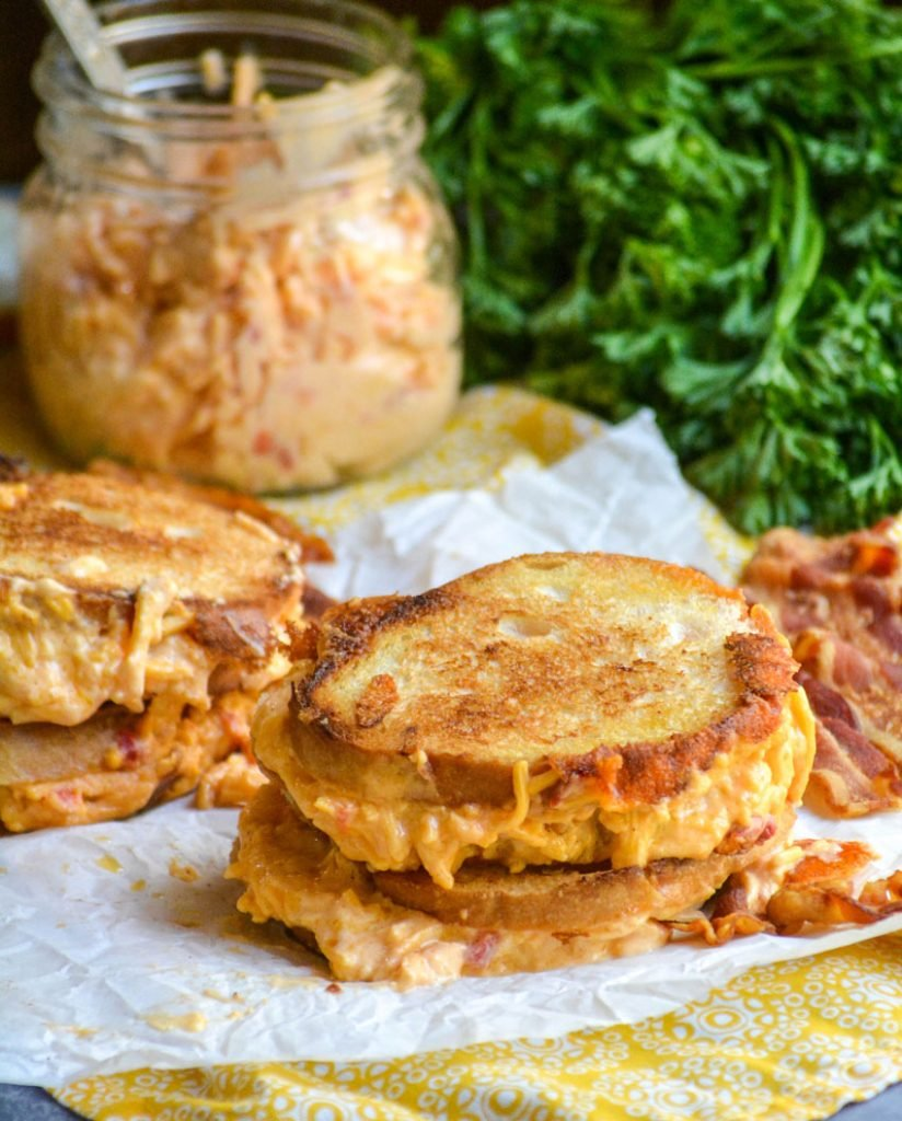 pimento cheese grilled cheese sandwiches shown on crinkled white parchment paper