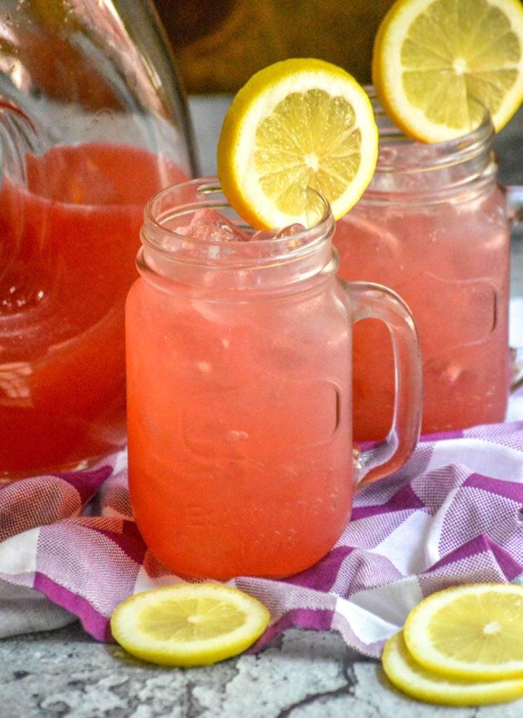 fresh blackberry lemonade served over ice in glass jars with a slice of lemon for garnish