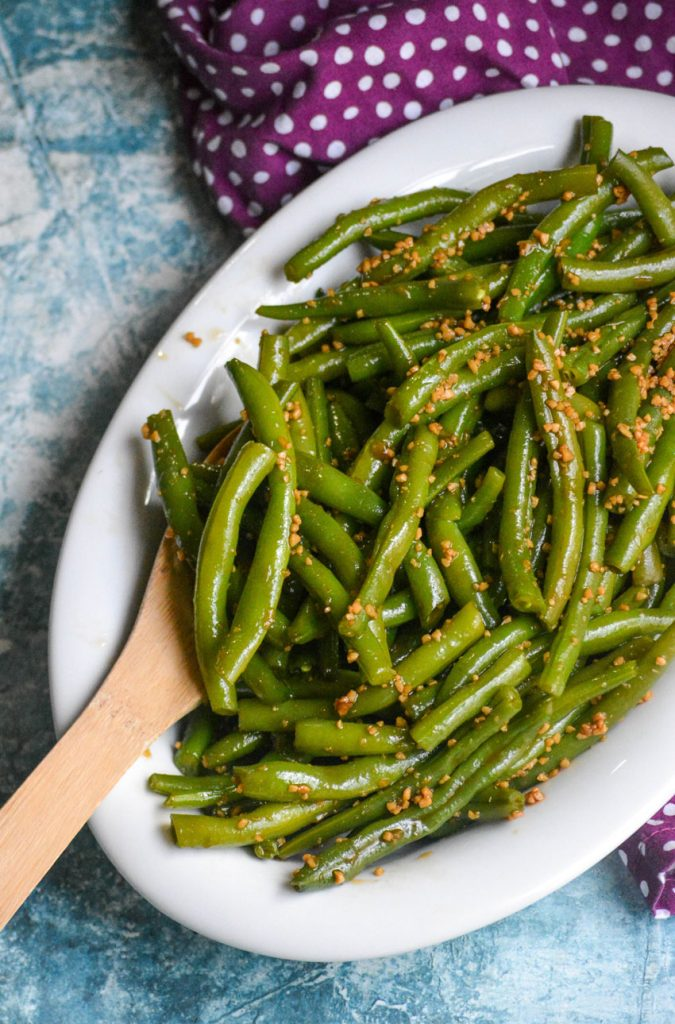 saucy garlic teriyaki green beans in a white serving dish with a wooden spoon