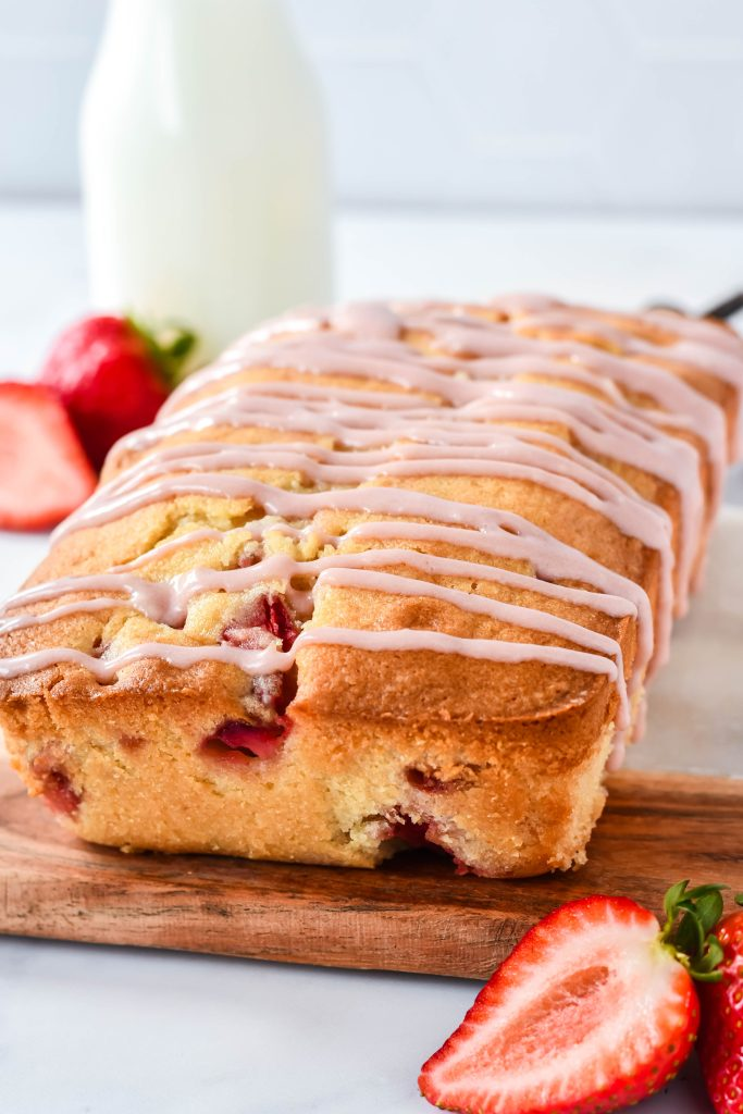 glazed strawberry bread served on a wooden cutting board