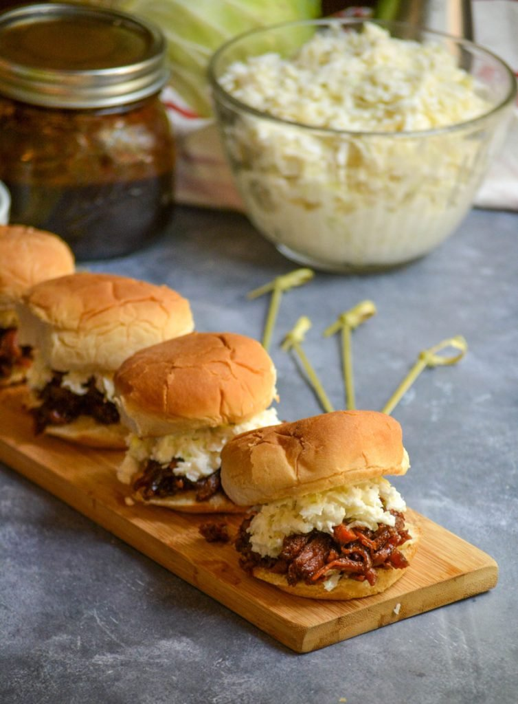several balsamic & honey pulled pork sliders served on a narrow wooden cutting board with coleslaw and extra barbecue sauce in the background