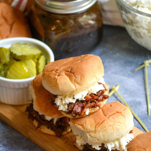 a stack of pulled pork sliders on a narrow wooden cutting board served with crisp dill pickle slices